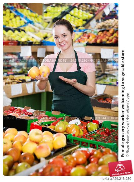 Купить «Female grocery worker welcoming to vegetable store», фото № 29215280, снято 14 октября 2017 г. (c) Яков Филимонов / Фотобанк Лори