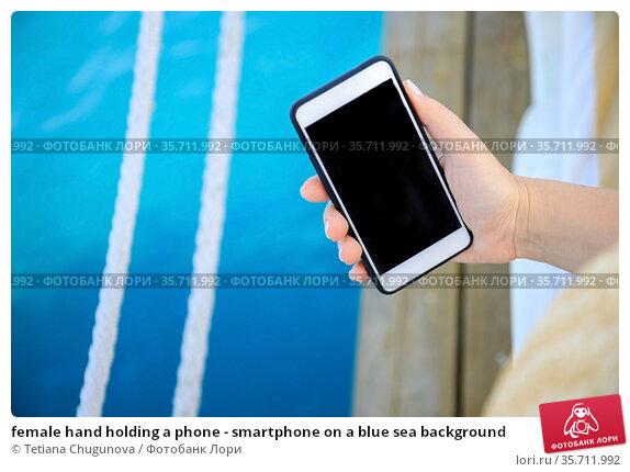 female hand holding a phone - smartphone on a blue sea background. Стоковое фото, фотограф Tetiana Chugunova / Фотобанк Лори