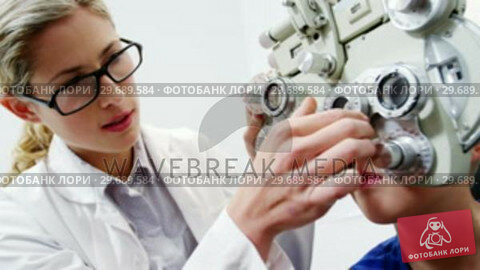 Купить «Female optometrist examining young patient on chiropter», видеоролик № 29689584, снято 20 июня 2016 г. (c) Wavebreak Media / Фотобанк Лори