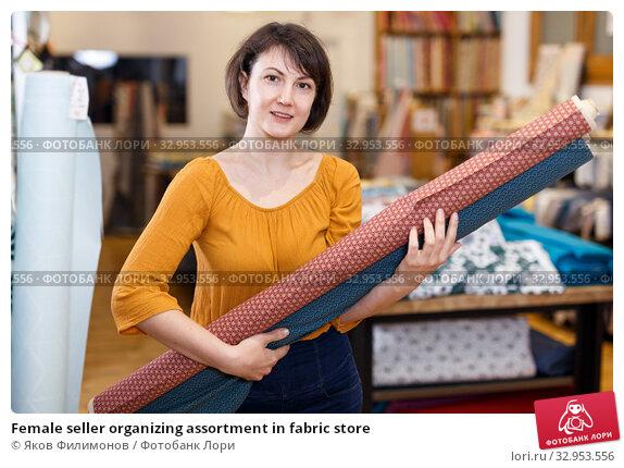 Female seller organizing assortment in fabric store. Стоковое фото, фотограф Яков Филимонов / Фотобанк Лори