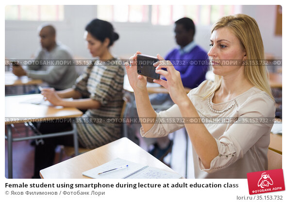 Female student using smartphone during lecture at adult education class. Стоковое фото, фотограф Яков Филимонов / Фотобанк Лори
