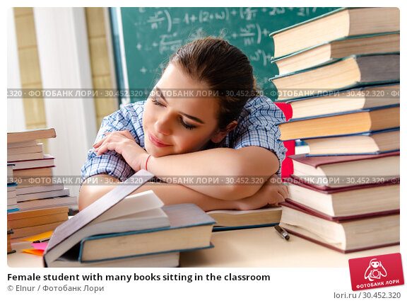 Female student with many books sitting in the classroom. Стоковое фото, фотограф Elnur / Фотобанк Лори