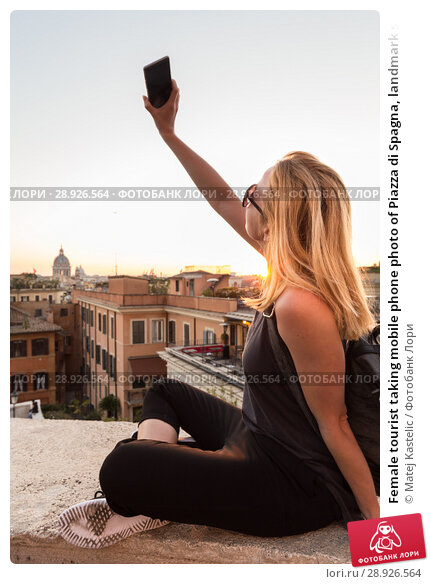 Купить «Female tourist taking mobile phone photo of Piazza di Spagna, landmark square with Spanish steps in Rome, Italy at sunset.», фото № 28926564, снято 21 августа 2018 г. (c) Matej Kastelic / Фотобанк Лори