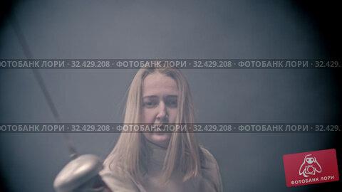 Купить «Fencing training - young woman fencer with long hair showing basics of fencing attacks», видеоролик № 32429208, снято 3 апреля 2020 г. (c) Константин Шишкин / Фотобанк Лори