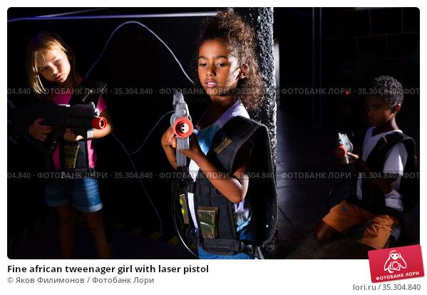 Fine african tweenager girl with laser pistol. Стоковое фото, фотограф Яков Филимонов / Фотобанк Лори
