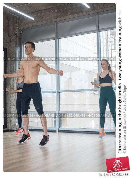 Fitness training in the bright studio - two young women training with their coach - jumping exercises. Стоковое фото, фотограф Константин Шишкин / Фотобанк Лори