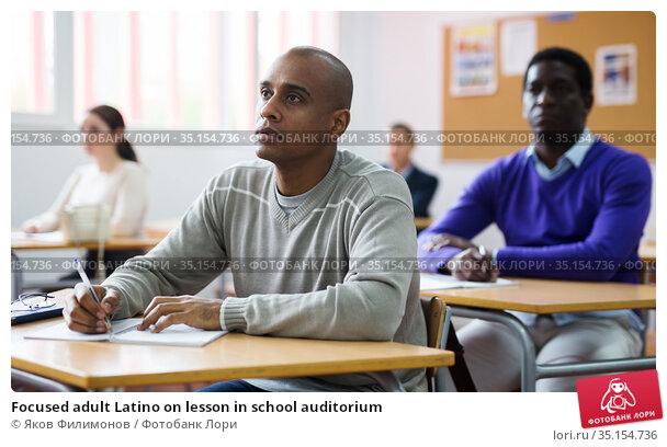 Focused adult Latino on lesson in school auditorium. Стоковое фото, фотограф Яков Филимонов / Фотобанк Лори