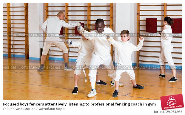 Купить «Focused boys fencers attentively listening to professional fencing coach in gym», фото № 29063956, снято 30 мая 2018 г. (c) Яков Филимонов / Фотобанк Лори
