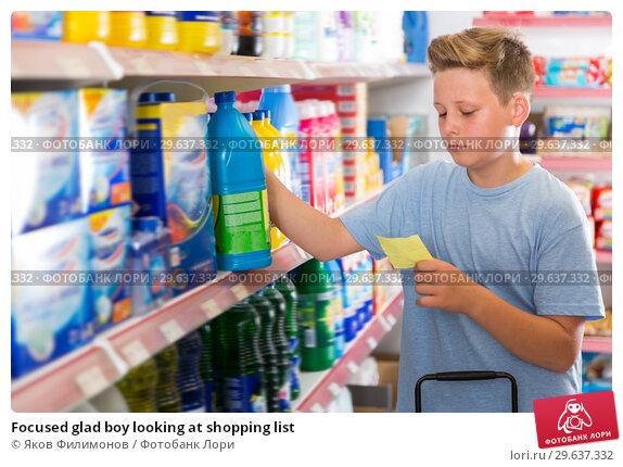 Купить «Focused glad boy looking at shopping list», фото № 29637332, снято 4 июня 2018 г. (c) Яков Филимонов / Фотобанк Лори