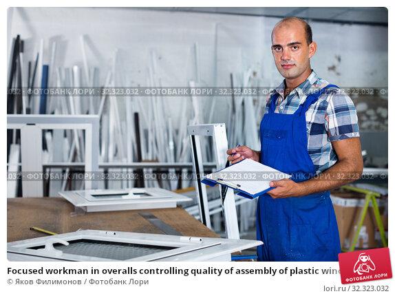 Купить «Focused workman in overalls controlling quality of assembly of plastic window in workshop», фото № 32323032, снято 19 июля 2017 г. (c) Яков Филимонов / Фотобанк Лори