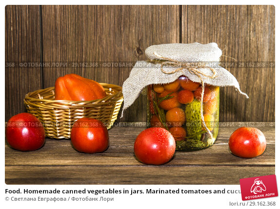 Купить «Food. Homemade canned vegetables in jars. Marinated tomatoes and cucumbers on the background of a wooden table in a rural style», фото № 29162368, снято 9 сентября 2018 г. (c) Светлана Евграфова / Фотобанк Лори