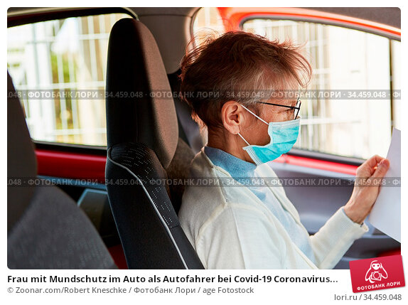 Frau mit Mundschutz im Auto als Autofahrer bei Covid-19 Coronavirus... Стоковое фото, фотограф Zoonar.com/Robert Kneschke / age Fotostock / Фотобанк Лори