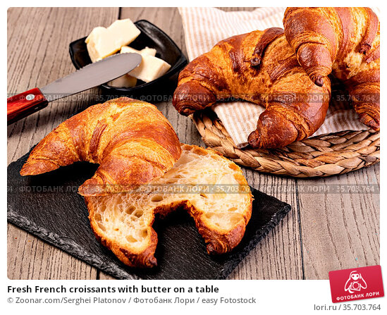 Fresh French croissants with butter on a table. Стоковое фото, фотограф Zoonar.com/Serghei Platonov / easy Fotostock / Фотобанк Лори
