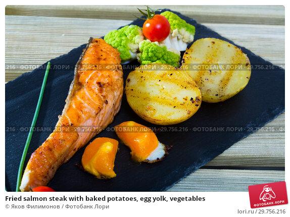 Купить «Fried salmon steak with baked potatoes, egg yolk, vegetables», фото № 29756216, снято 18 февраля 2019 г. (c) Яков Филимонов / Фотобанк Лори
