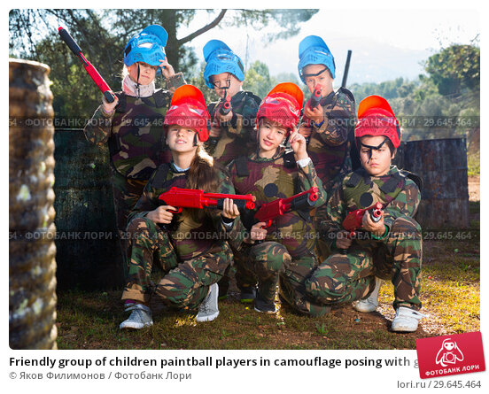 Купить «Friendly group of children paintball players in camouflage posing with guns on paintball playing field outdoors», фото № 29645464, снято 24 ноября 2018 г. (c) Яков Филимонов / Фотобанк Лори