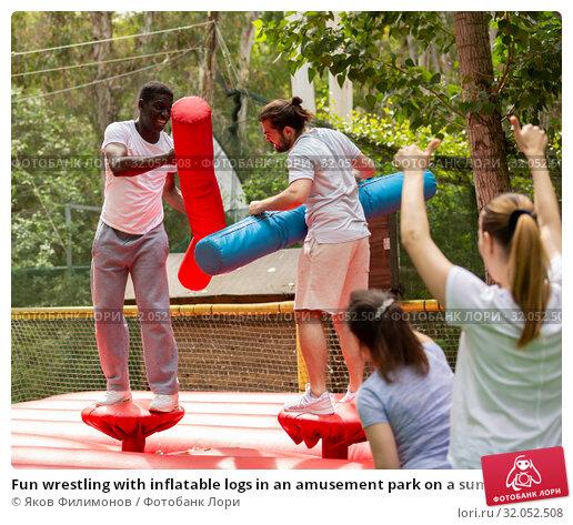 Fun wrestling with inflatable logs in an amusement park on a summer sunny day. Стоковое фото, фотограф Яков Филимонов / Фотобанк Лори