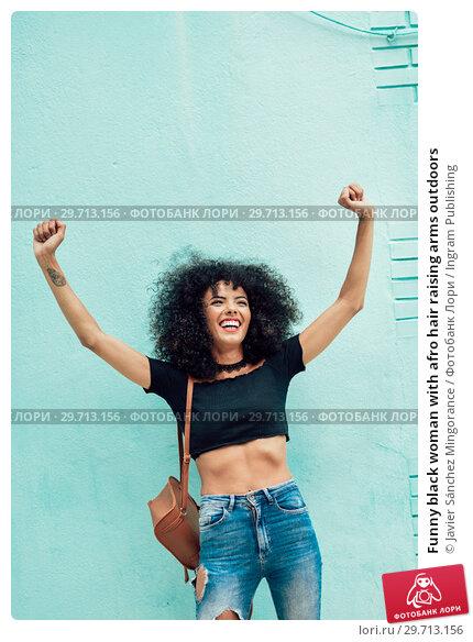 Купить «Funny black woman with afro hair raising arms outdoors», фото № 29713156, снято 23 мая 2018 г. (c) Ingram Publishing / Фотобанк Лори