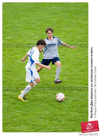 Футбол.Два игрока на зелёном газоне и мяч., фото № 320572, снято 12 июня 2008 г. (c) Федор Королевский / Фотобанк Лори