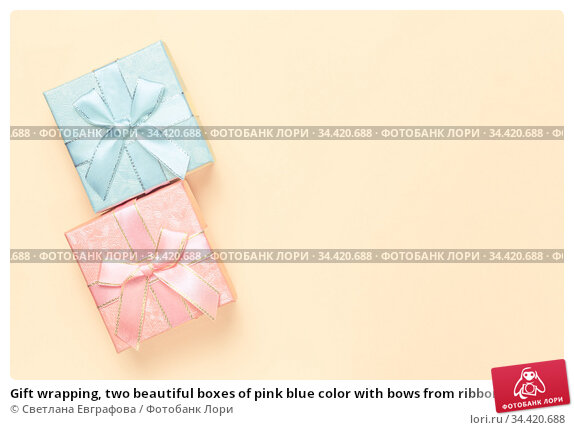 Gift wrapping, two beautiful boxes of pink blue color with bows from ribbons for the holiday on a beige peach background in pastel colors with copy space top view, flatlay. Стоковое фото, фотограф Светлана Евграфова / Фотобанк Лори