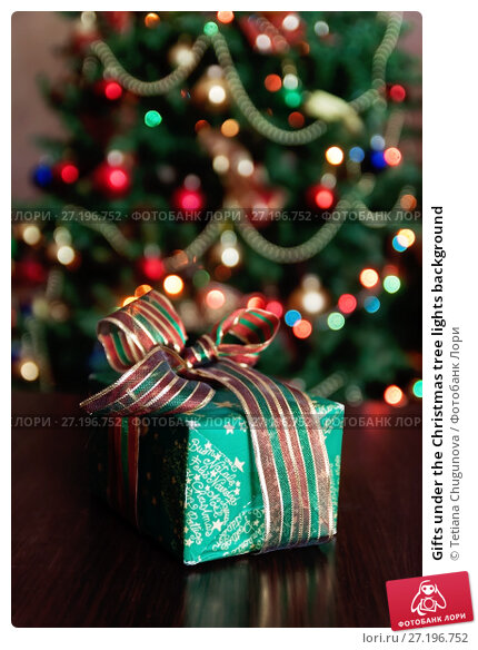 Купить «Gifts under the Christmas tree lights background», фото № 27196752, снято 12 мая 2017 г. (c) Tetiana Chugunova / Фотобанк Лори