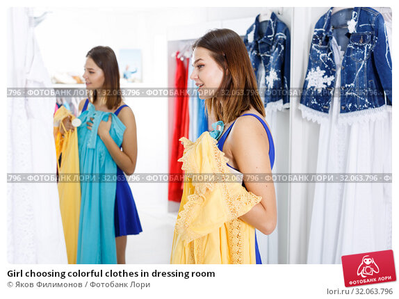Girl choosing colorful clothes in dressing room. Стоковое фото, фотограф Яков Филимонов / Фотобанк Лори