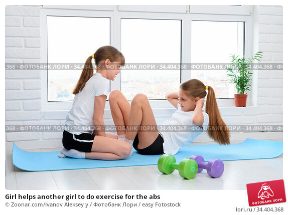 Girl helps another girl to do exercise for the abs. Стоковое фото, фотограф Zoonar.com/Ivanov Aleksey y / easy Fotostock / Фотобанк Лори