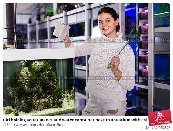 Girl holding aquarian net and water container next to aquarium with colorful fish in aquarium shop. Стоковое фото, фотограф Яков Филимонов / Фотобанк Лори