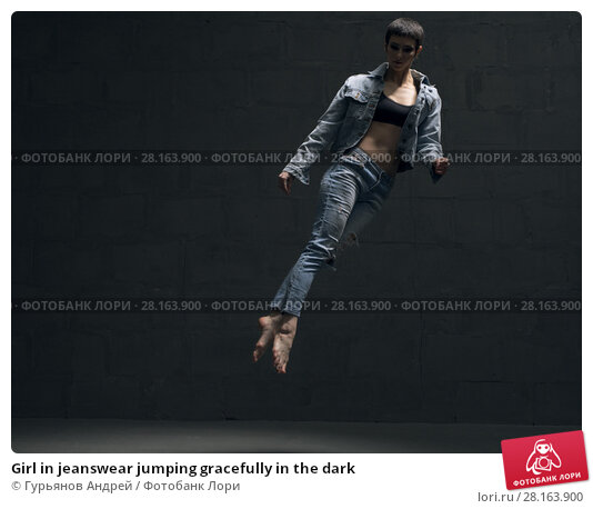 Купить «Girl in jeanswear jumping gracefully in the dark», фото № 28163900, снято 2 марта 2018 г. (c) Гурьянов Андрей / Фотобанк Лори
