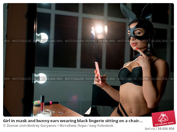 Girl in mask and bunny ears wearing black lingerie sitting on a chair... Стоковое фото, фотограф Zoonar.com/Andrey Guryanov / easy Fotostock / Фотобанк Лори