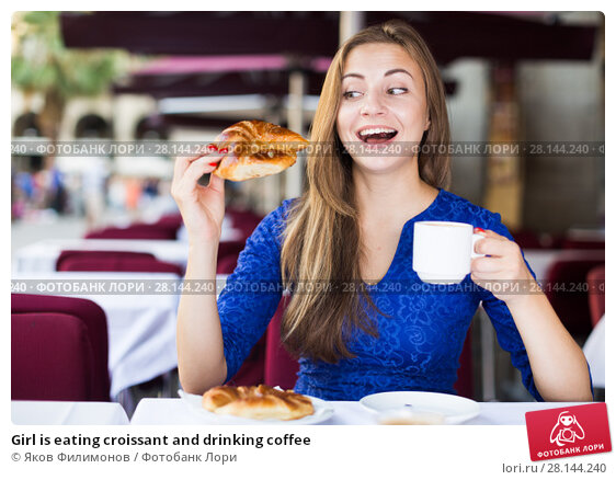 Купить «Girl is eating croissant and drinking coffee», фото № 28144240, снято 30 июля 2017 г. (c) Яков Филимонов / Фотобанк Лори