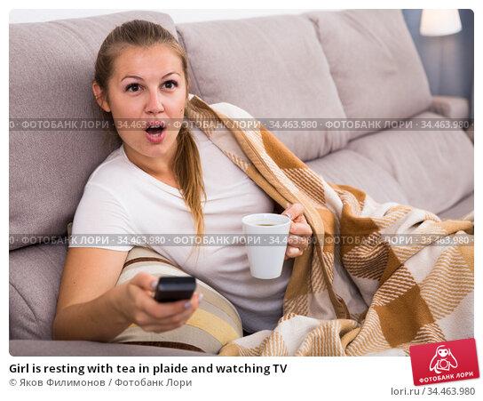 Girl is resting with tea in plaide and watching TV. Стоковое фото, фотограф Яков Филимонов / Фотобанк Лори