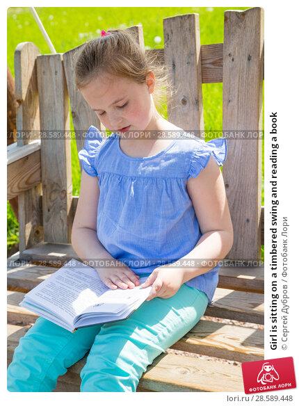 Купить «Girl is sitting on a timbered swing and reading a book», фото № 28589448, снято 11 июня 2017 г. (c) Сергей Дубров / Фотобанк Лори