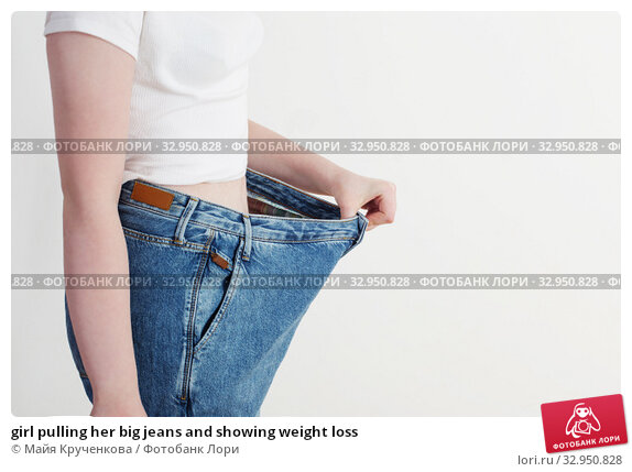 girl pulling her big jeans and showing weight loss. Стоковое фото, фотограф Майя Крученкова / Фотобанк Лори