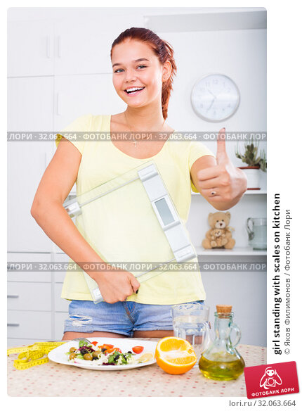 girl standing with scales on kitchen. Стоковое фото, фотограф Яков Филимонов / Фотобанк Лори