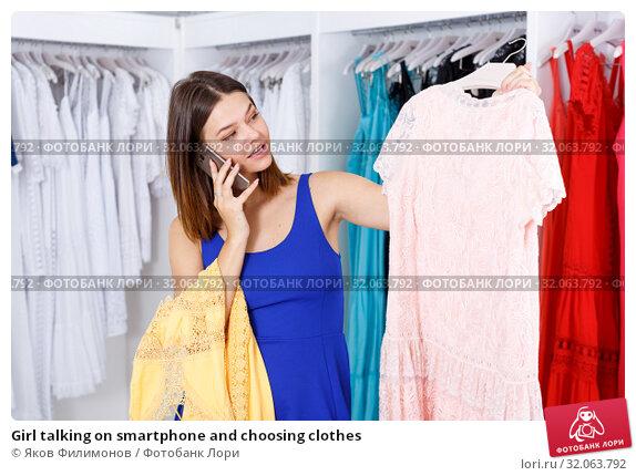 Girl talking on smartphone and choosing clothes. Стоковое фото, фотограф Яков Филимонов / Фотобанк Лори