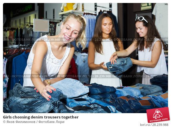 Купить «Girls choosing denim trousers together», фото № 28239988, снято 25 марта 2019 г. (c) Яков Филимонов / Фотобанк Лори