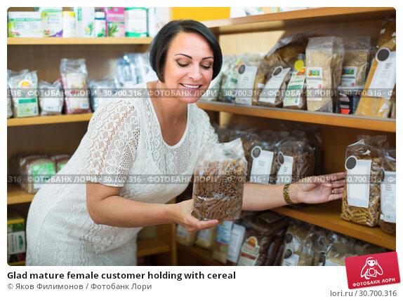 Купить «Glad mature female customer holding with cereal», фото № 30700316, снято 17 июля 2019 г. (c) Яков Филимонов / Фотобанк Лори