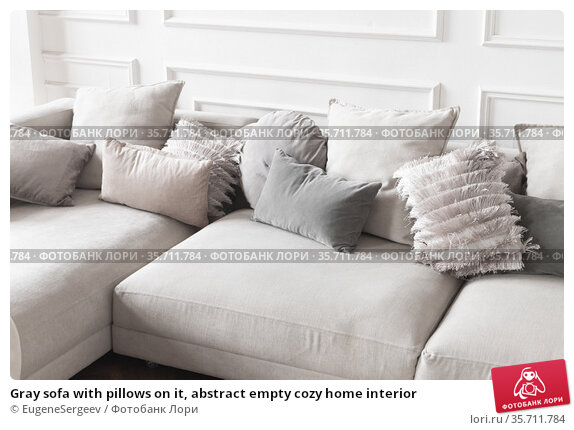 Gray sofa with pillows on it, abstract empty cozy home interior. Стоковое фото, фотограф EugeneSergeev / Фотобанк Лори
