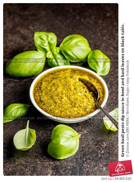Green basil pesto dip sauce in bowl and basil leaves on black table. Стоковое фото, фотограф Zoonar.com/JIRI HERA / easy Fotostock / Фотобанк Лори