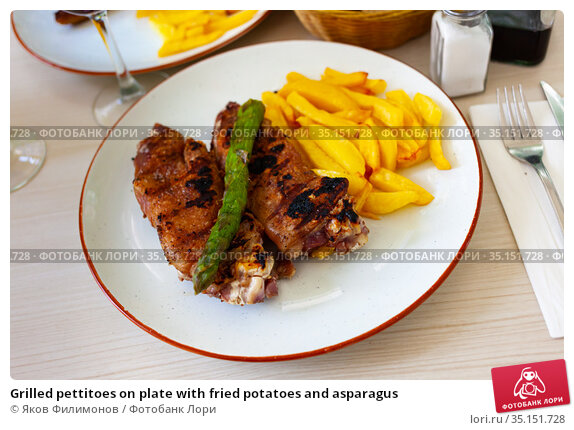Grilled pettitoes on plate with fried potatoes and asparagus. Стоковое фото, фотограф Яков Филимонов / Фотобанк Лори