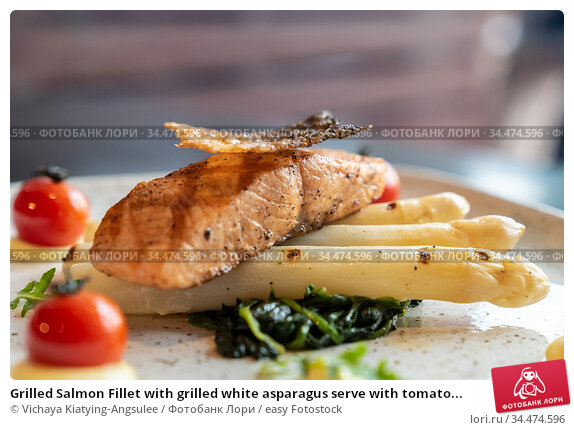 Grilled Salmon Fillet with grilled white asparagus serve with tomato... Стоковое фото, фотограф Vichaya Kiatying-Angsulee / easy Fotostock / Фотобанк Лори