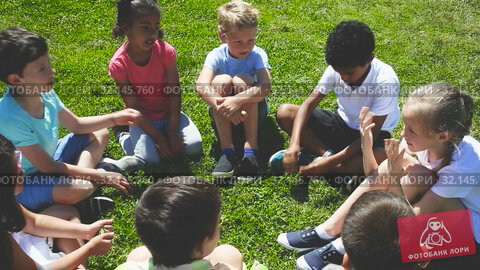 Купить «Group of elementary school children chatting on the green lawn», видеоролик № 32145760, снято 7 июня 2019 г. (c) Яков Филимонов / Фотобанк Лори