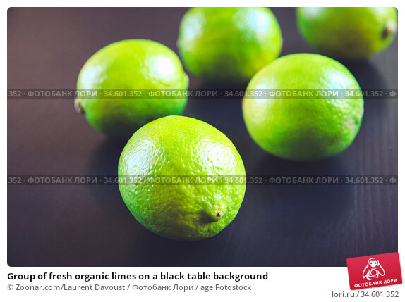 Group of fresh organic limes on a black table background. Стоковое фото, фотограф Zoonar.com/Laurent Davoust / age Fotostock / Фотобанк Лори