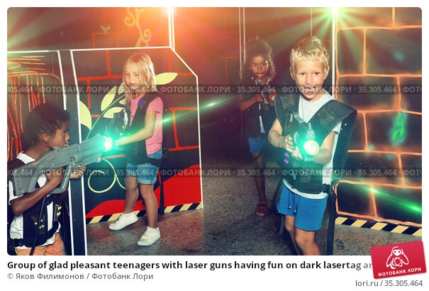 Group of glad pleasant teenagers with laser guns having fun on dark lasertag arena. Стоковое фото, фотограф Яков Филимонов / Фотобанк Лори