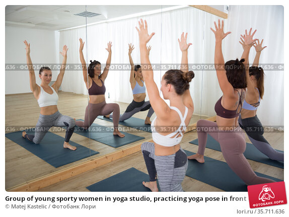Group of young sporty women in yoga studio, practicing yoga pose in front of the mirror. Healthy active lifestyle, working out indoors in gym. Стоковое фото, фотограф Matej Kastelic / Фотобанк Лори