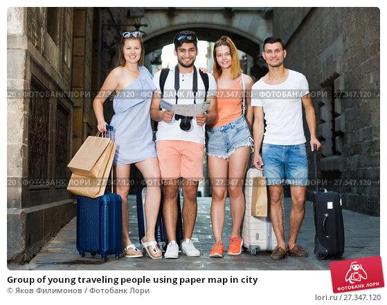Купить «Group of young traveling people using paper map in city», фото № 27347120, снято 22 июня 2017 г. (c) Яков Филимонов / Фотобанк Лори