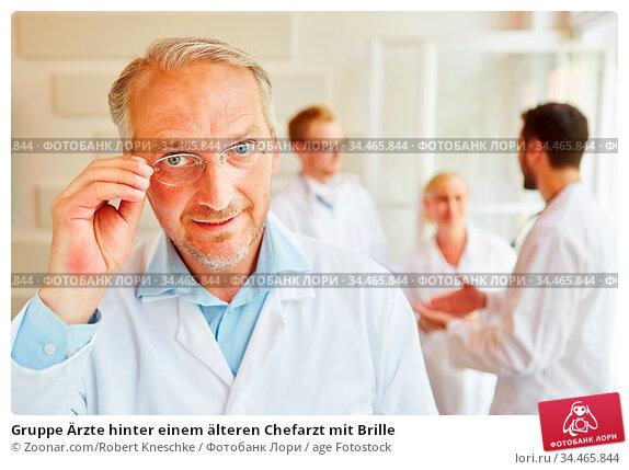 Gruppe Ärzte hinter einem älteren Chefarzt mit Brille. Стоковое фото, фотограф Zoonar.com/Robert Kneschke / age Fotostock / Фотобанк Лори