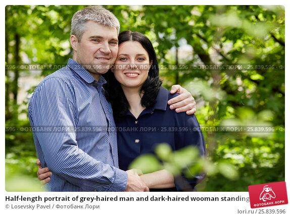 Купить «Half-length portrait of grey-haired man and dark-haired wooman standing embraced in summer park», фото № 25839596, снято 22 мая 2016 г. (c) Losevsky Pavel / Фотобанк Лори