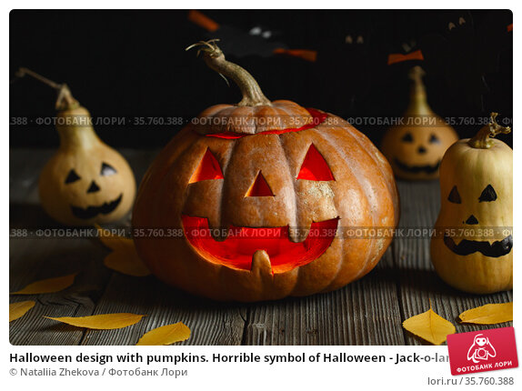Halloween design with pumpkins. Horrible symbol of Halloween - Jack-o-lantern. Scary head of pumpkin with flame and a few small painted gourds. Glowing face, trick or treat. Стоковое фото, фотограф Nataliia Zhekova / Фотобанк Лори
