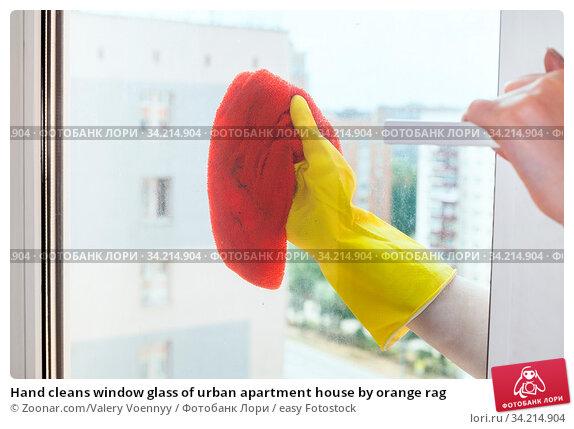 Hand cleans window glass of urban apartment house by orange rag. Стоковое фото, фотограф Zoonar.com/Valery Voennyy / easy Fotostock / Фотобанк Лори